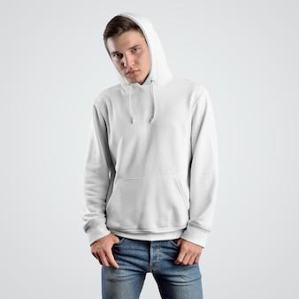 フードの若い男に白いパーカーのモックアップテンプレートの正面図。店頭で発表するファッションデザイン。