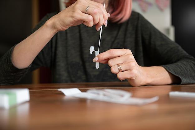 빠른 자가 집 covid 19 테스트를 만드는 여성의 전면 모습 - 면봉을 용액에 담그고 있습니다.