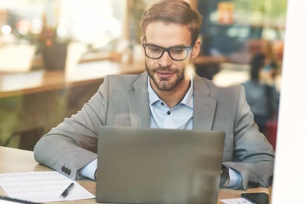 일하는 동안 노트북을 사용하는 바쁜 백인 사업가 또는 남성 프리랜서의 전면