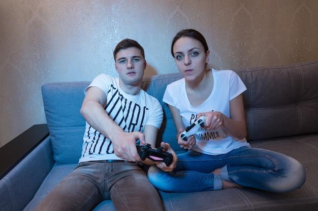 집에서 함께 소파에 앉아 치열한 경쟁적인 표정으로 비디오 게임을 하는 젊은 부부의 전면 모습