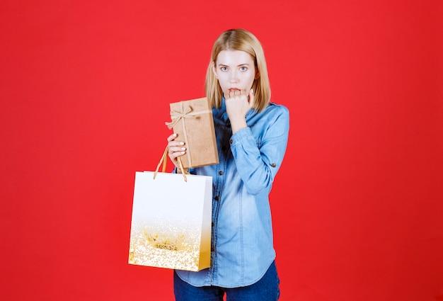 쇼핑 가방과 선물을 들고 빨간 벽에 그녀의 손을 물고 젊은 무서워 소녀의 전면보기