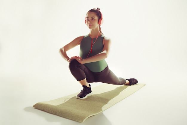 体操のクラスで体を伸ばす若い女性の正面図。