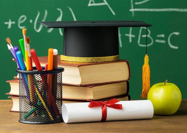 Вид спереди академической шапки с книгами и карандашами