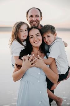 어린 딸과 아들이 있는 사랑스럽고 매력적인 웃는 가족의 전면 모습