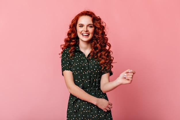 분홍색 배경에 고립 된 사랑스러운 생강 소녀의 전면 모습. 카메라보고 웃는 곱슬 젊은 여자의 스튜디오 샷.