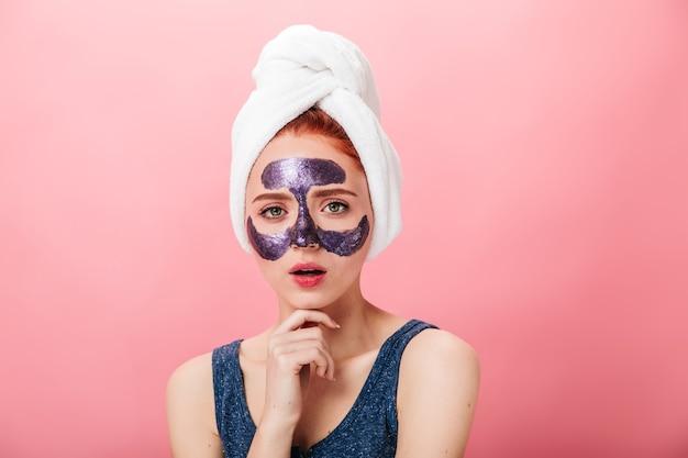 스파 치료를 하 고 사랑스러운 여자의 전면 모습입니다. 분홍색 배경에 고립 된 얼굴 마스크와 멋진 백인 아가씨의 스튜디오 샷.