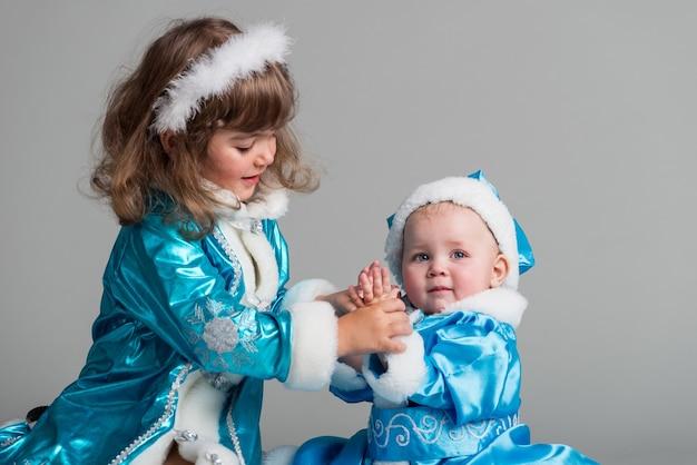 스노우 메이든 의상을 입은 사랑스러운 어린 소녀의 전면 모습. 프리미엄 사진