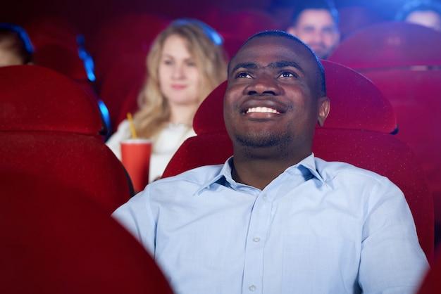 映画館で面白い映画を見ているアフリカの男性視聴者の正面図。映画のファイナルを期待して青いシャツを着ている若いアフロ男。エンターテインメントとレジャーの概念。