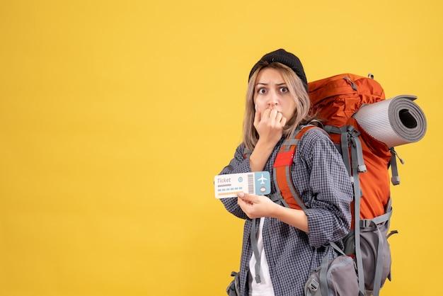 チケットを保持しているバックパックと興奮した旅行者の女性の正面図