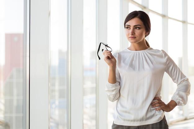 Вид спереди соблазнительной бизнес-леди, позирующей в очках