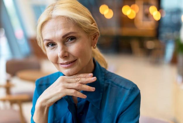 仕事に出ながらポーズをとって魅力的な年上のビジネス女性の正面図