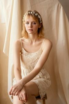 春の花の冠をかぶってポーズをとる魅力的な女性の正面図