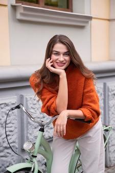 야외에서 그녀의 자전거와 함께 포즈를 취하는 매혹적인 여자의 전면보기