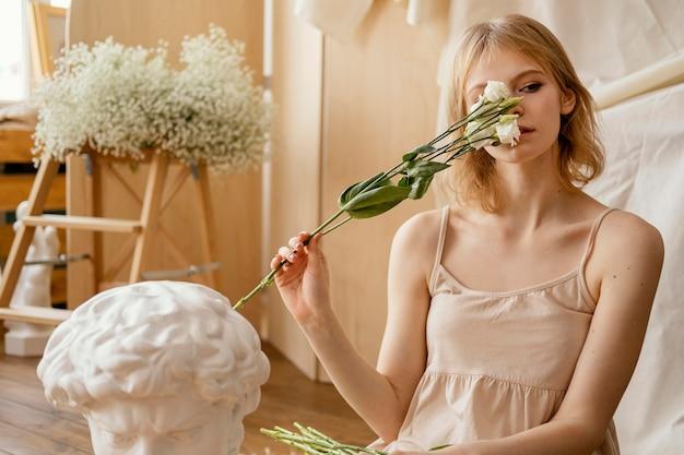 봄 꽃과 함께 포즈를 취하는 매혹적인 여자의 전면보기 프리미엄 사진