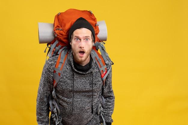黄色の壁に立っている革の手袋とバックパックを持つ驚いた男性のヒッチハイカーの正面図
