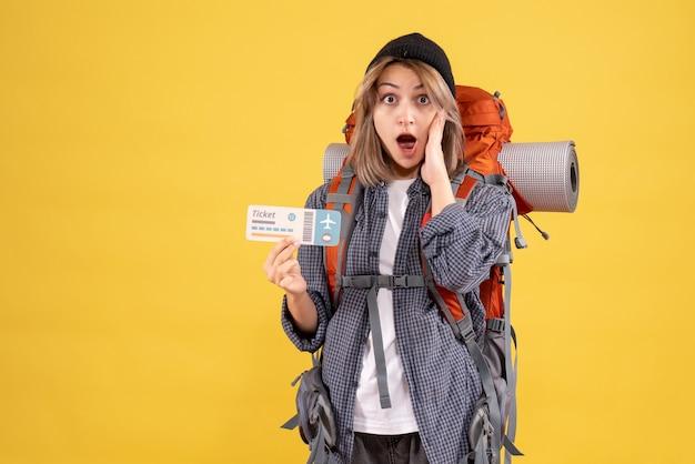 チケットを保持しているバックパックと驚いた旅行者の女性の正面図