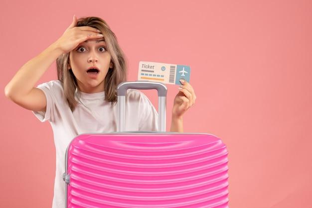 Вид спереди изумленной молодой девушки с розовым чемоданом, держащей билет