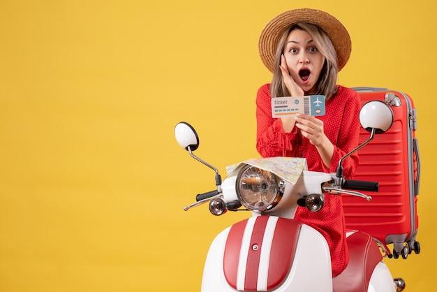 原付のチケットを保持している赤いドレスを着た驚いた若い女性の正面図