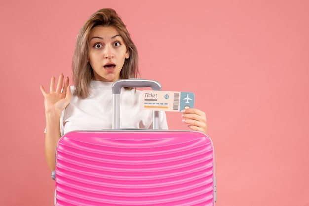 Вид спереди изумленной молодой женщины с розовым чемоданом, держащей билет