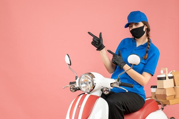 パステル ピーチの背景に注文を配達するスクーターに座って医療用マスクと手袋を身に着けている野心的な宅配便の女の子の正面図