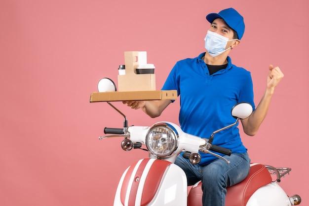 パステル調の桃の背景に注文を配達するスクーターに座っている帽子をかぶったマスクを着た野心的な男性配達員の正面図