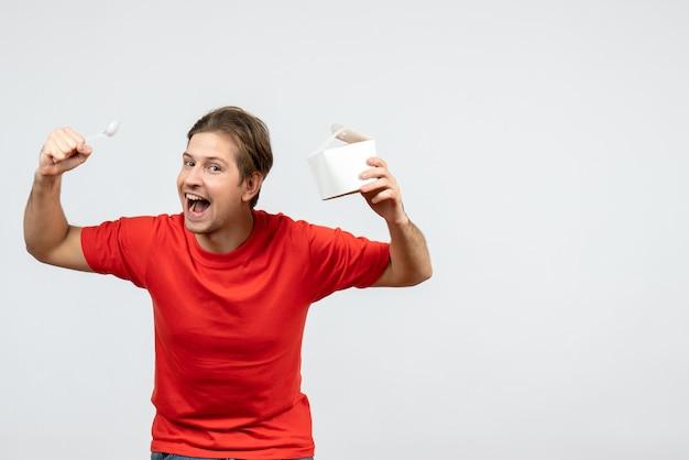 白い背景の上の紙箱とスプーンを保持している赤いブラウスの野心的な若い男の正面図