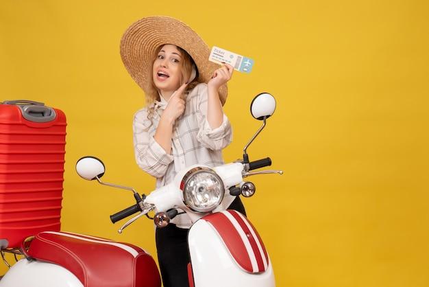 Вид спереди амбициозной молодой женщины в шляпе, собирающей свой багаж, сидя на мотоцикле и показывая билет