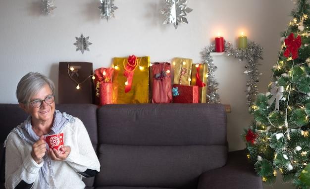 クリスマスツリーとプレゼントを背景にソファに座っている白髪の老婆の正面図。お茶を飲みながらリラックスする1人の高齢者
