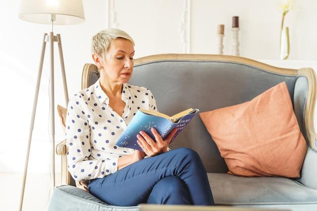 긴 의자에서 책을 읽는 데 집중하는 우아한 단발머리 여성의 전면 모습