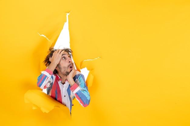 노란 종이에 찢어진 구멍을 통해 올려다 보는 감정적이고 미친 지친 젊은 남자의 전면보기