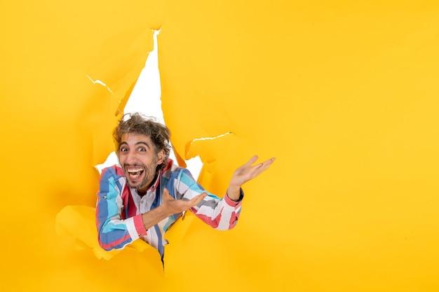 노란 종이에 찢어진 구멍을 통해 카메라를 위해 포즈를 취하는 감정적이고 미친 젊은 남자의 전면 보기 무료 사진