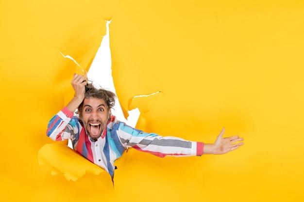 노란 종이에 찢어진 구멍을 통해 카메라를 위해 포즈를 취하는 감정적이고 미친 젊은 남자의 전면 보기