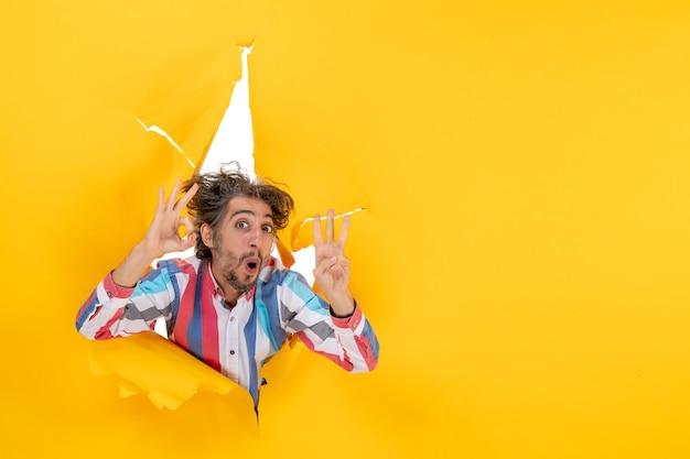 노란 종이에 찢어진 구멍을 통해 세 가지를 보여주는 감정적이고 미친 젊은 남자의 전면 보기