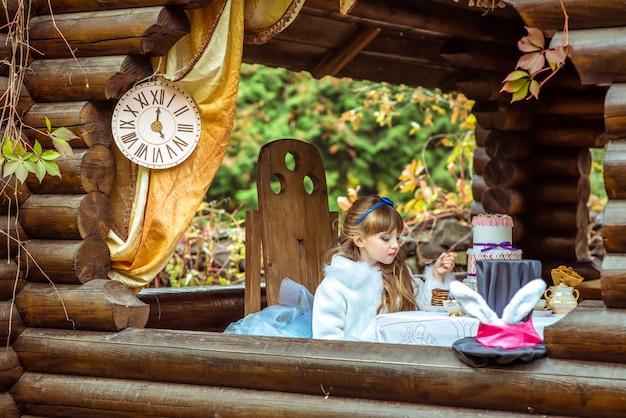 테이블에 숟가락에 케이크 한 조각을 들고 작은 아름다운 소녀의 전면보기