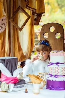 Вид спереди маленькая красивая девушка в декорации, пить чай за столом в парке
