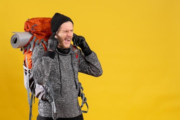 革手袋と指で耳を閉じるバックパックと怒っている男性のヒッチハイカーの正面図