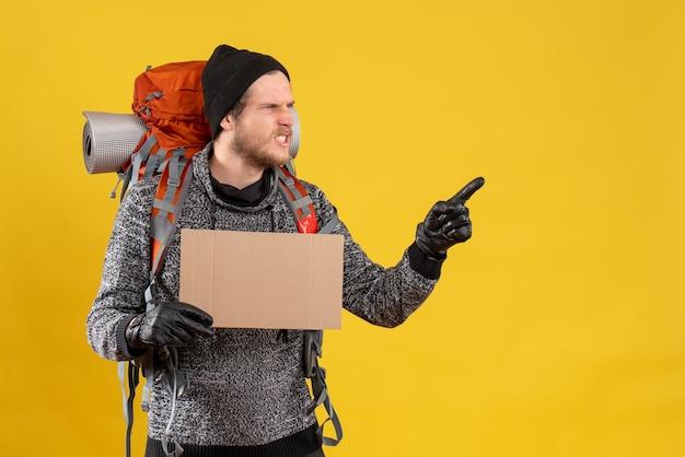 革の手袋と正しい方向を指している空白の段ボールを保持しているバックパックと怒っている男性のヒッチハイカーの正面図