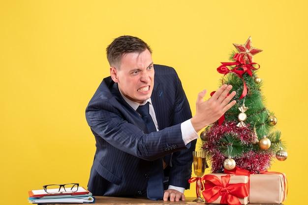 Вид спереди разгневанного человека, стоящего за столом возле елки и подарков на желтой стене