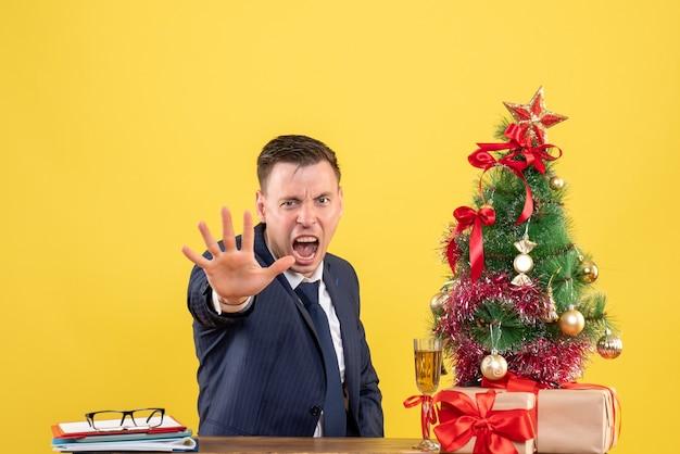 Вид спереди сердитого человека, останавливающего руку, сидящего за столом возле рождественской елки и подарков на желтой стене