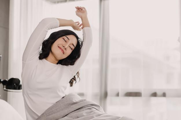 Вид спереди азиатской женщины в утре. она вытягивает руку и тело на кровати