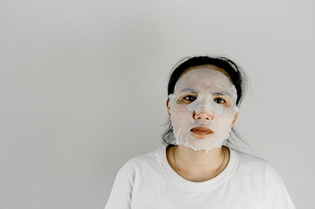 白いtシャツを着て、シートマスクで顔を覆っているアジアの女性の正面図。