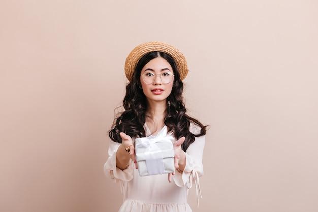 생일 선물을 가진 아시아 여자의 전면 모습입니다. 선물 상자를 들고 밀 짚 모자에 중국 여자입니다.