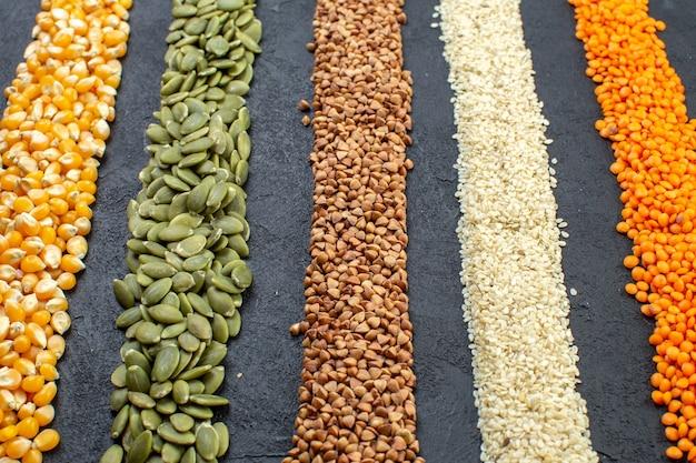 검은 배경에 메밀 호박 씨앗 옥수수 쌀의 모듬 곡물의 전면 보기