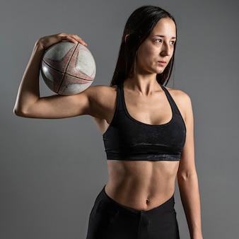 Вид спереди спортивного женского регбиста, держащего мяч