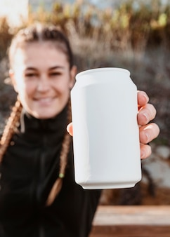 ソーダ缶を示す運動女性の正面図