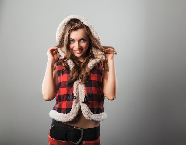 市松模様のセーターベストのボンネットに触れる魅力的な陽気な女性の正面図。
