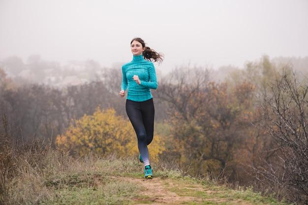가을 안개 낀 숲에서 조깅하는 매력적인 건강한 맞는 젊은 여자의 전면 모습.