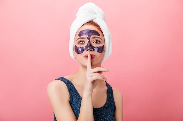 スパトリートメントをしながら秘密の兆候を示す魅力的な女性の正面図。ピンクの背景に分離されたフェイスマスクを持つかわいい女の子のスタジオショット。