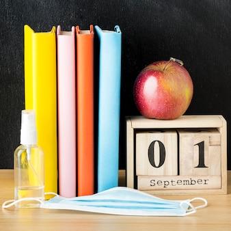 Вид спереди обратно в школу предметов первой необходимости с книгами и яблоком