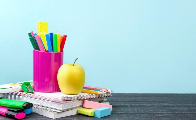 Вид спереди обратно в школу канцелярских товаров с яблоком и карандашами